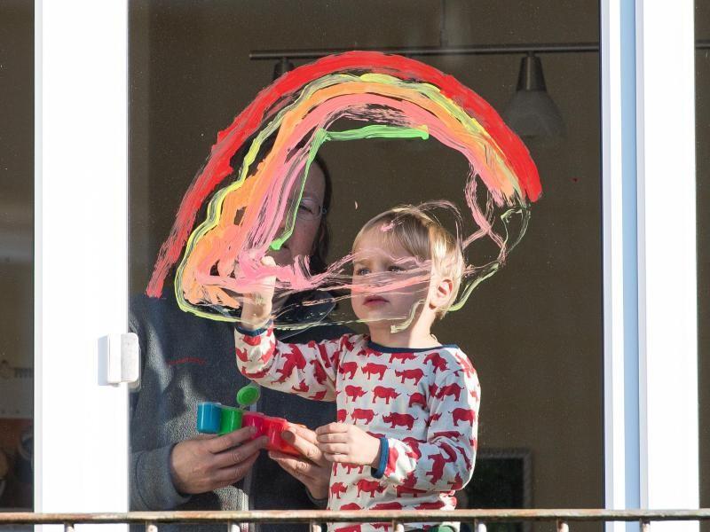 Kind malt Regenbogen ans Fenster