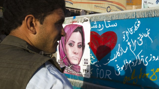 Afghan man walks past an election poster of parliamentary candidate Barkazi on a traditional taxi in Herat, western Afghanistan