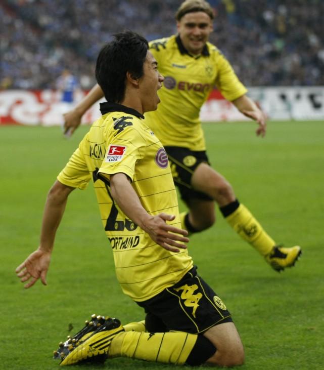 Borussia Dortmund's Kagawa and Schmelzer celebrate a goal against Schalke 04 during the German Bundesliga soccer match in Gelsenkirchen