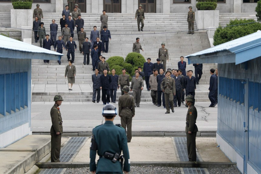 North Korean officials visit the truce village of Panmunjom as a South Korean soldier keeps watching the north from the south side of the concrete border in the demilitarized zone separating the two Koreas in Paju
