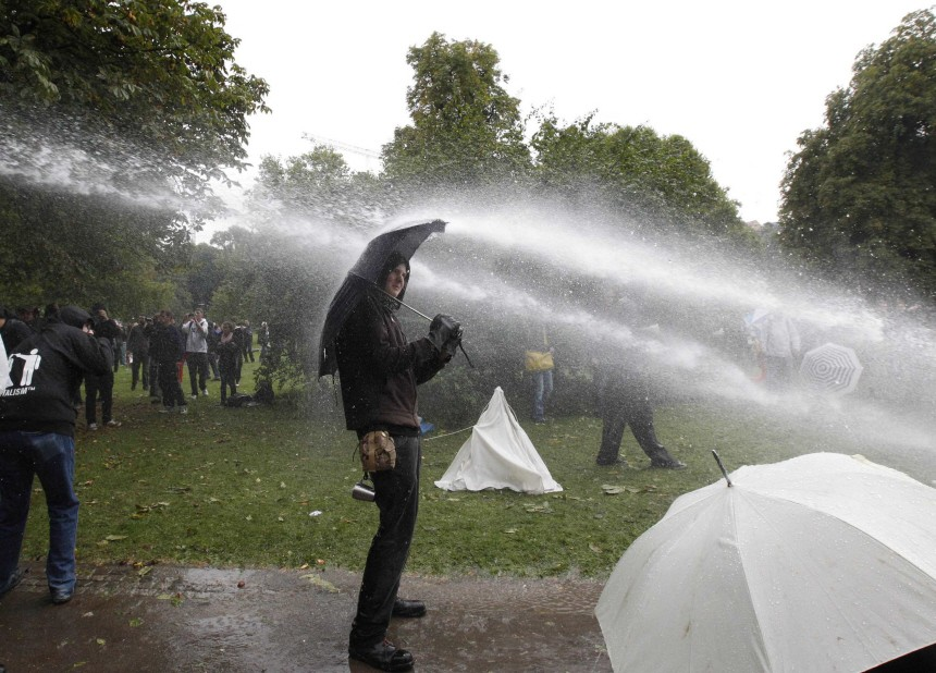 Policemen use water canons to remove protestors from a park next to the Stuttgart train station