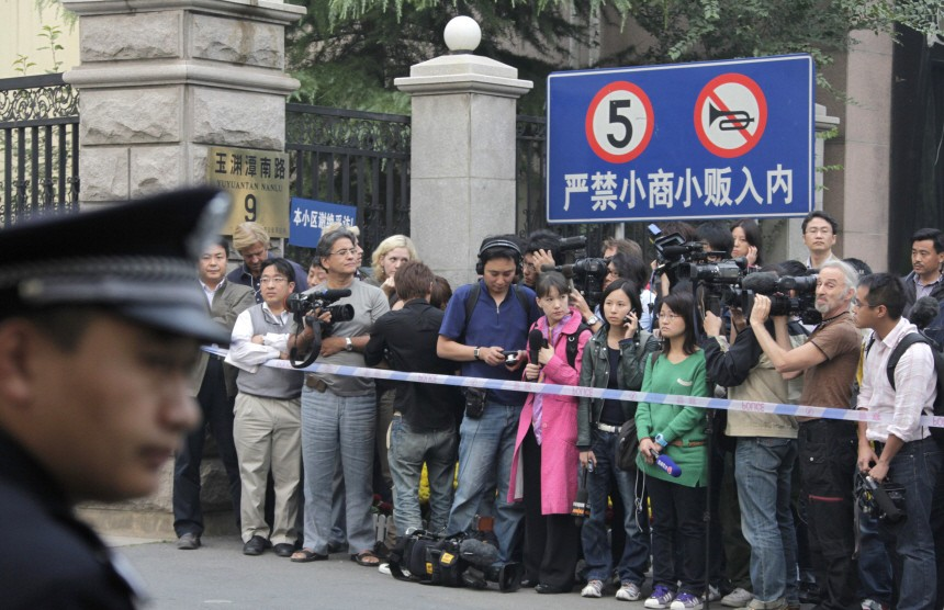 A policeman guards as reporters wait at the entrance of a residential compound where Liu Xia lives, in Beijing