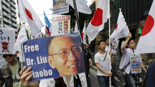Protesters holds a picture of Nobel Peace Prize laureate Liu Xiaobo of China during an anti-Chinese rally in Tokyo