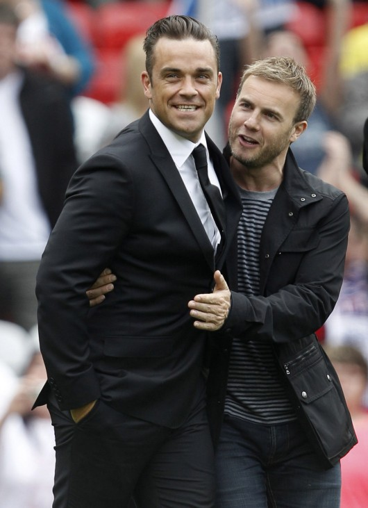 British pop star Robbie Williams walks onto the pitch with singer Gary Barlow before the Unicef Soccer Aid charity match in Manchester