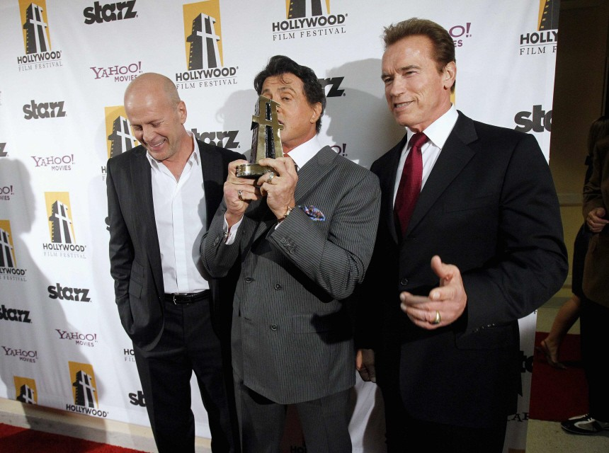 Stallone holds his Hollywood Career Achievement Award, as he poses with California Governor Schwarzenegger and Willis, in Beverly Hills