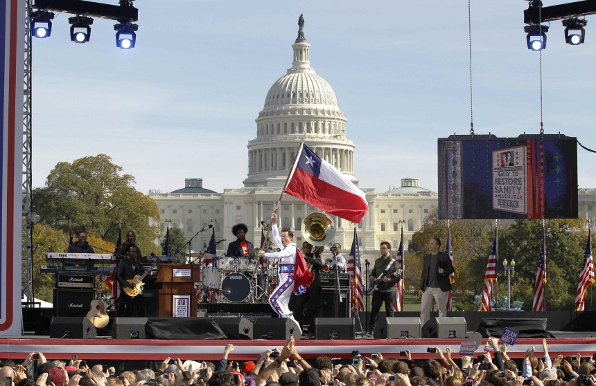 Comedian Colbert runs across the stage with a flag on the National Mall in Washington at the 'Rally to Restore Sanity and/or Fear'