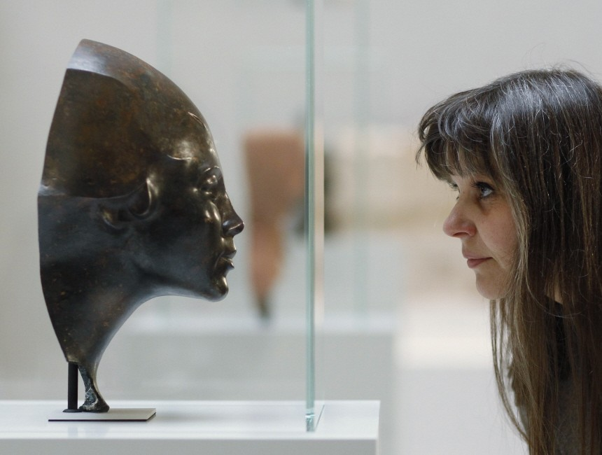 Journalist inspects sculpture that was discovered during archAeological excavations in central Berlin