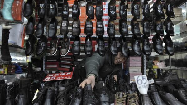 A vendor arranges leather shoes at a market in Shenyang