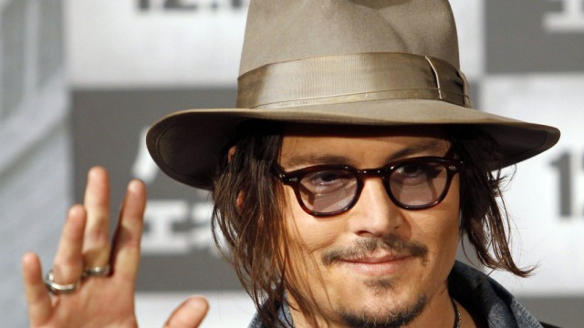 U.S. actor Depp waves at a photo session prior to a news conference to promote his movie 'Public Enemies' in Tokyo