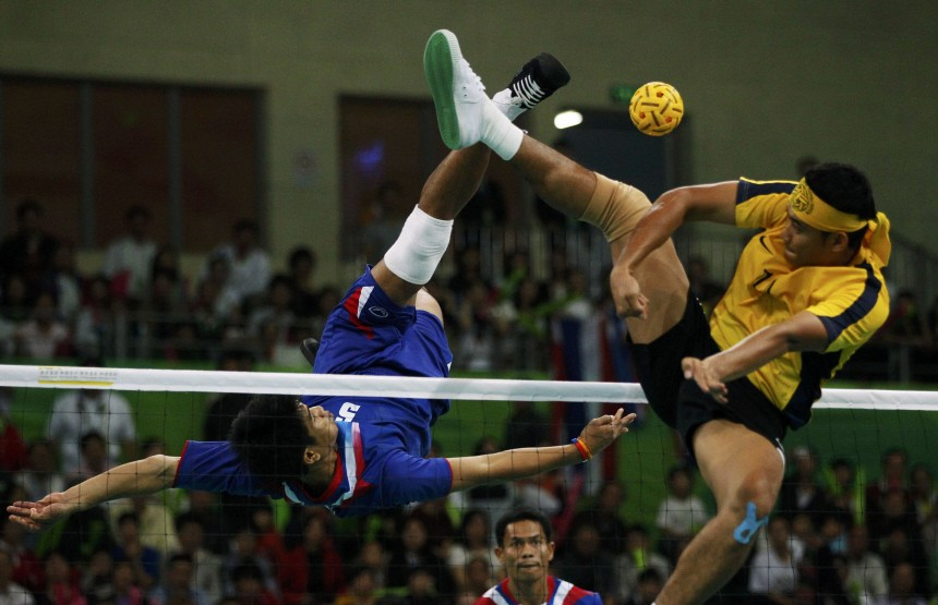 Thailand's Pornchai Kaokaew executes an overhead kick against Malaysia's Norshahruddin Mad Ghani during their sepak takraw men's team final at the 16th Asian Games in Guangzhou