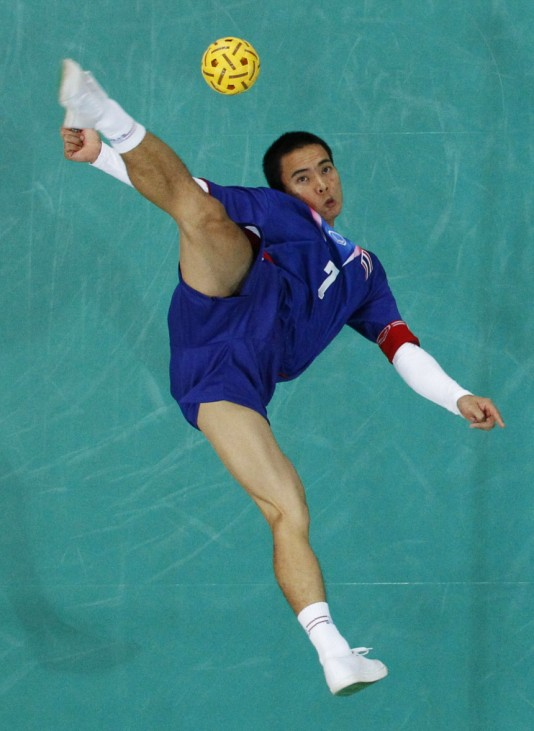 Thailand's Pattarapong Yupadee executes an overhead kick against Malaysia during their sepak takraw men's team final at the 16th Asian Games in Guangzhou