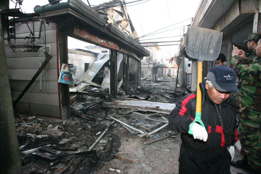 A man walks past a house wrecked by artillery shells fired by North Korea on Yeonpyeong Island