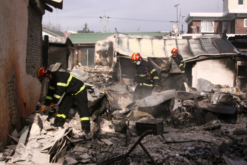Firefighters check damaged house on Yeonpyeong Island after the island was hit  by artillery shells fired by North Korea