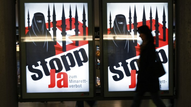Woman passes display on the initiative against the construction of new minarets in Switzerland in Bern
