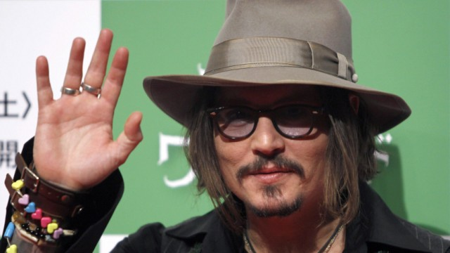 Actor Johnny Depp waves at a photo session to promote the movie Alice in Wonderland in Tokyo