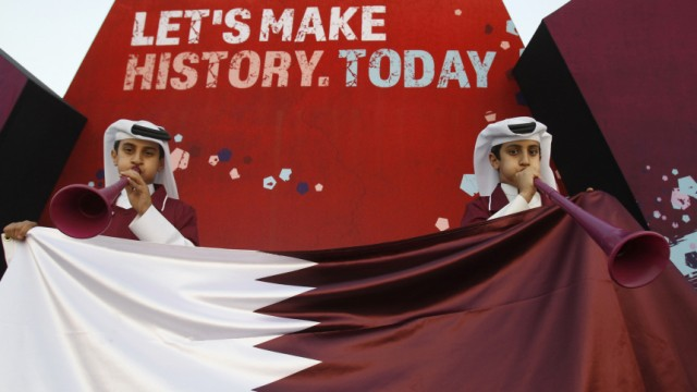Qatari fans blow vuvuzelas before the announcement of the hosts for the 2022 World Cup, in Souq Waqif