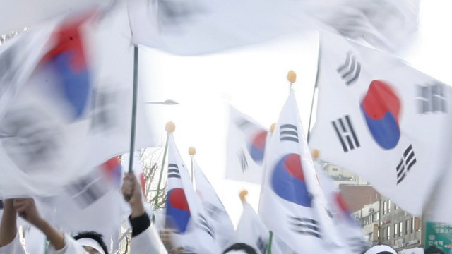 People hold South Korean flags and shout for independence at an anniversary re-enactment in Seoul