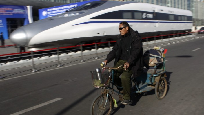 A resident rides a tricycle past the head of a CRH Harmony bullet train outside an exhibition for the Seventh World Congress on High Speed Rail in Beijing A resident rides a tricycle past the head of