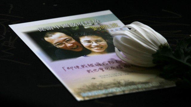 A postcard of Nobel Peace Prize winner Liu and his wife is seen on the desk set up by pro-democracy Civic Party to collect signatures from passers-by to demand his release in Hong Kong