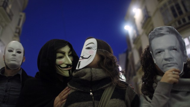 WikiLeaks supporters wear masks during a demonstration in Malaga