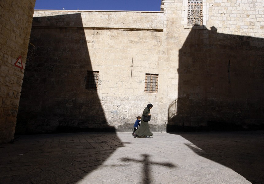 A Palestinian woman walks with a child past a shadow of a cross cast by the Church of the Nativity in Bethlehem