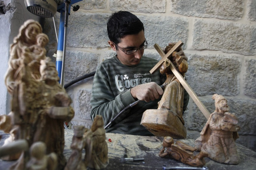 A Palestinian carpenter carves a wooden statue of the Virgin Mary and baby Jesus in a workshop in Bethlehem