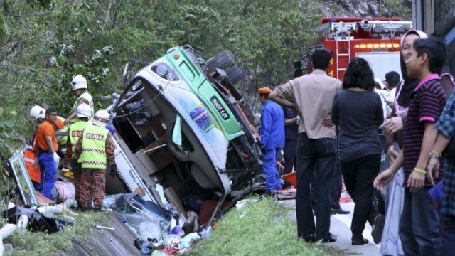 Rescue personnel work on the wreckage of a tour bus on a highway in Pos Slim