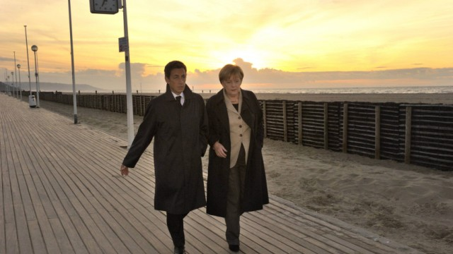 France's President Sarkozy and German Chancellor Merkel walk at a beach in Deauville