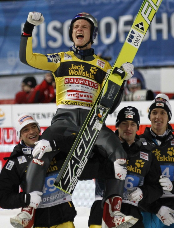 Austria's Thomas Morgenstern is lifted by team mates Kofler and Loitzl after winning four-hills ski jumping tournament in Bischofshofen
