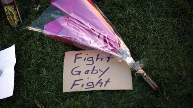 A sign referring to wounded congresswoman Gabrielle Giffords is seen at a makeshift memorial outside the hospital where she is recovering in Tucson