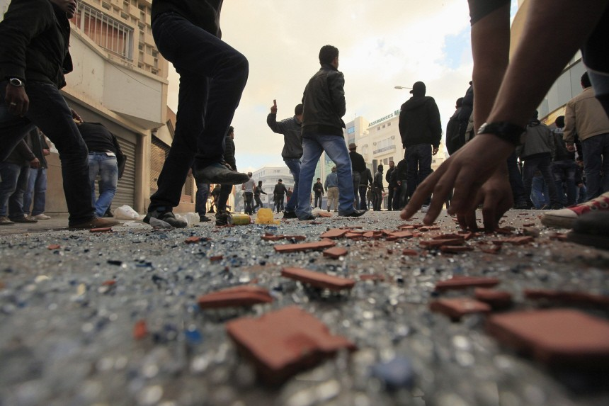 Rioters throw stones during clashes with riot police in Tunis