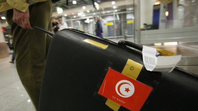 A German tourist pulls his suitcase after returning to Duesseldorf airport from Tunis
