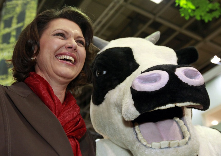 German Agriculture Minister Aigner poses with person dressed in cow costume as she visits Internationale Gruene Woche IGW fair in Berlin