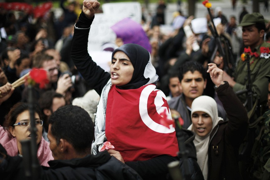 A woman gestures in front of the headquarters of the Constitutional Democratic Rally party of ousted president Zine al-Abidine Ben Ali during a demonstration in downtown Tunis