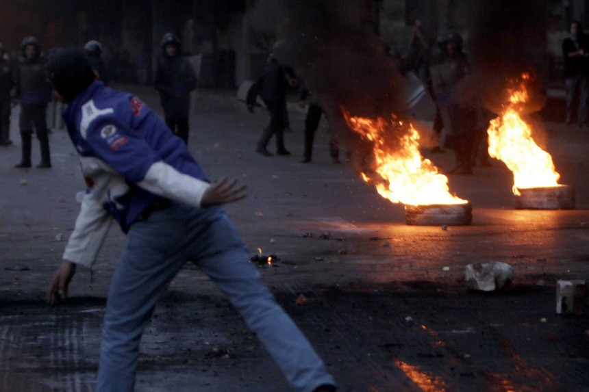 Anti-government protesters clash with riot police near burning tyres placed as a barricade during clashes in Cairo