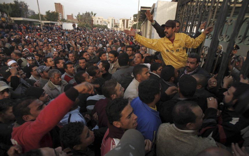 People attempt to enter the hospital grounds to retrieve his body in the port city in Suez