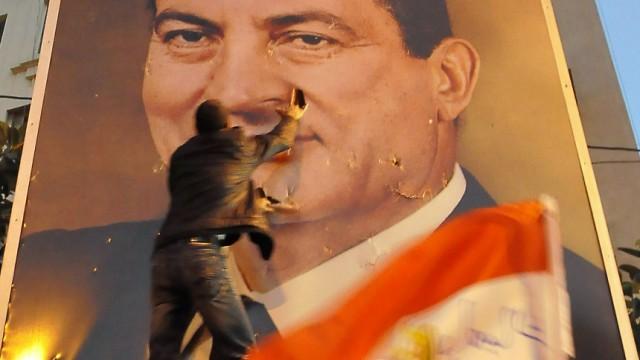 Aufruhr in Ägypten: Demonstranten in Kairo reißen ein Plakat von Staatschef Mubarak von der Wand. Der Präsident versucht die Proteste auszusitzen.