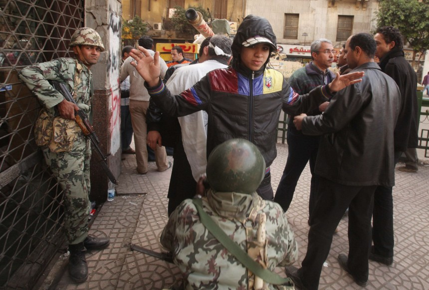 An Egyptian soldier searches a protester during an anti-Mubarak protest in Cairo
