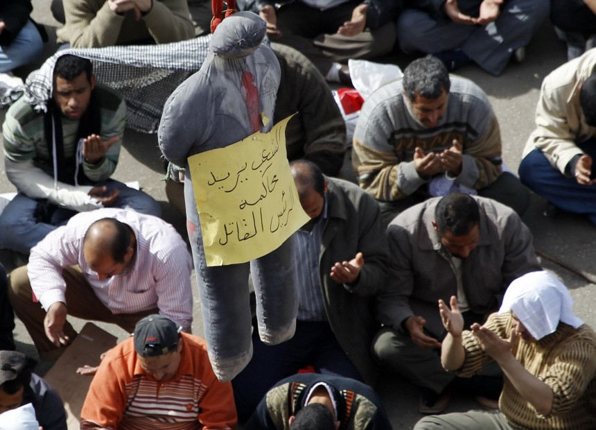 Anti-government protesters take part in Friday prayers next to an effigy of Egypt's President Hosni Mubarak at Tahrir Square in Cairo
