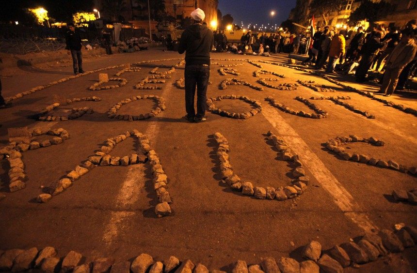 Stones placed by protesters to form the phrase 'go out' in different languages are seen at Tahrir Square in Cairo