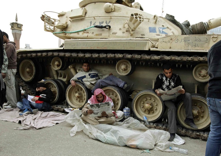 Anti-government supporters rest by an Egyptian army tank in Tahrir Square in Cairo