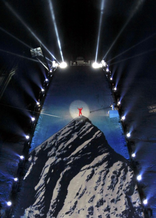 A performer pulled by ropes stands on the jumping hill on the top of a projection of Germany's Zugspitze mountain during the opening ceremony of the Alpine Ski World Championship in Garmisch-Partenkirchen