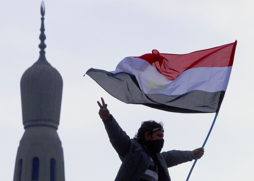 An opposition supporter flashes the victory sign as he holds an Egyptian flag atop a lamp post near a mosque in Tahrir Square in Cairo