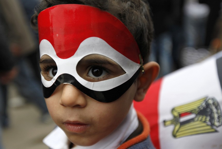 A young anti-government protester wears an Egyptian flag mask during demonstrations inside Tahrir Square in Cairo