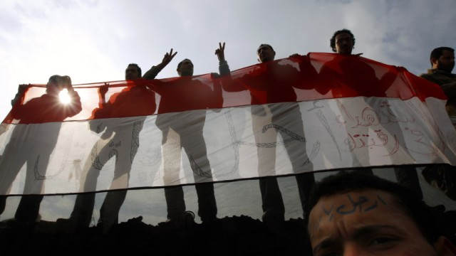Anti-government protesters wave an Egyptian flag during a mass demonstration in Tahrir Square in Cairo