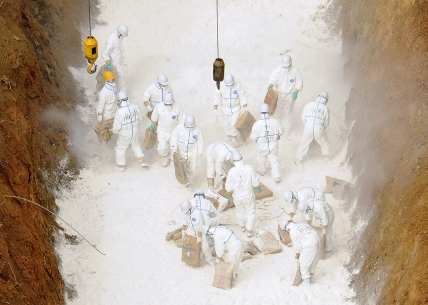 Workers wearing protective suits prepare to dispose of culled chickens in Kinokawa