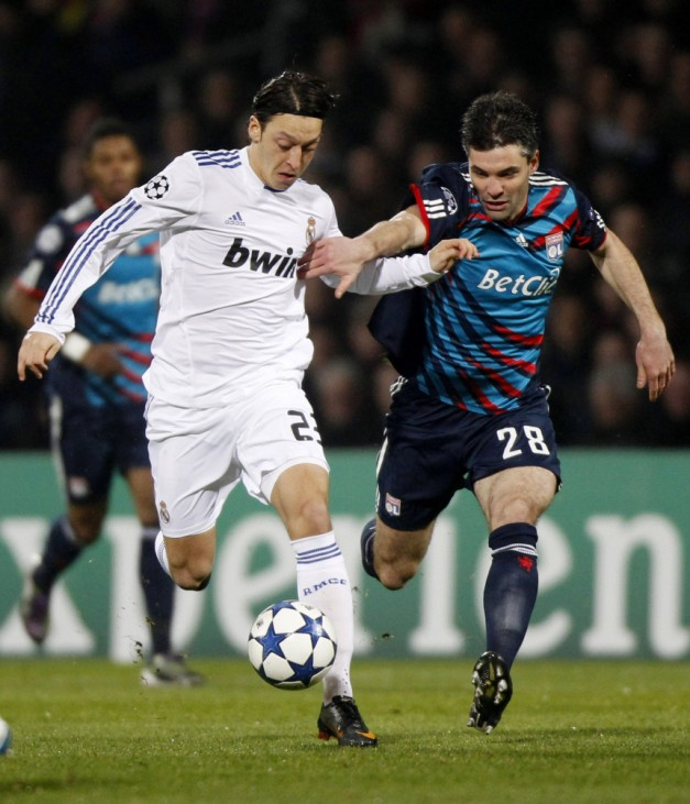Olympique Lyon's Toulalan challenges Real Madrid's Oezil during their Champions League soccer match in Lyon