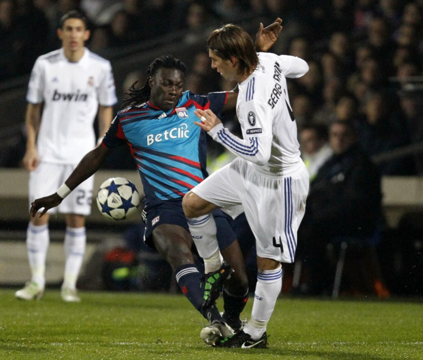 Olympique Lyon's Gomis challenges Ramos of Real Madrid during their Champions League soccer match in Lyon