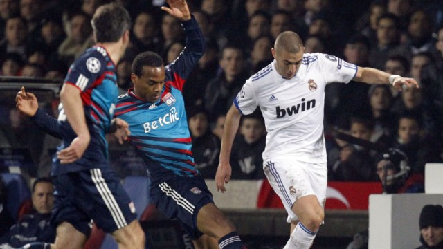 Olympique Lyon's Briand challenges Benzema of Real Madrid during their Champions League soccer match in Lyon
