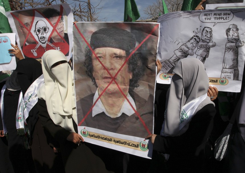 Hamas supporters hold posters depicting a crossed-out portrait of Libyan leader Muammar Gaddafi during a rally in Gaza City against the Libyan leader